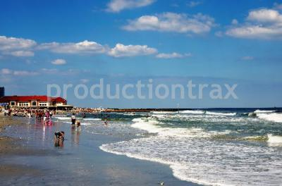 Atlantic City New Jersey Ocean Beach with green water and white waves on the right and hotels and swimmer on the ltft on a summer sunny day blue sky white clouds